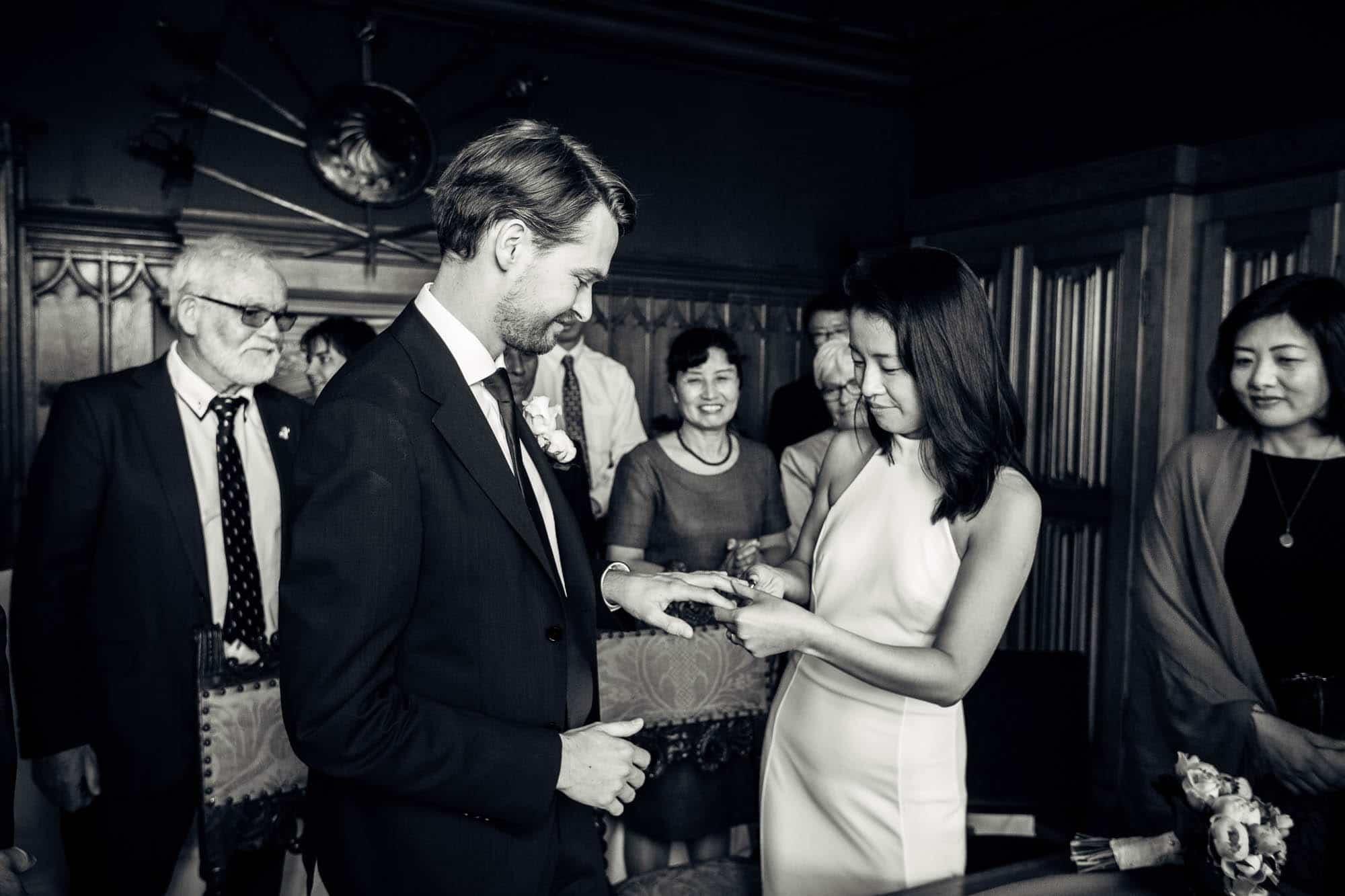 Asiatische Braut steckt Ehering dem Bräutigam an