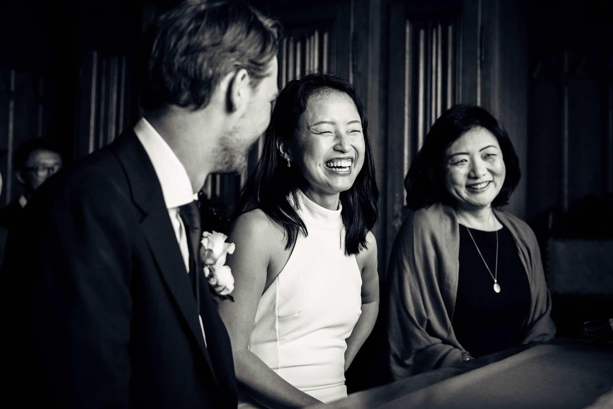 Braut, Trauzeugin und Bräutigam lachen