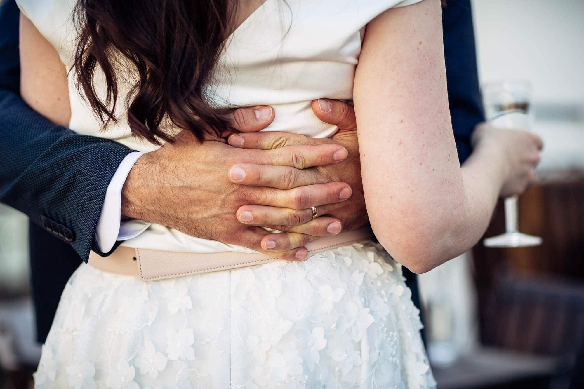 Bräutigam umarmt Braut. Hände und Ehering Detail