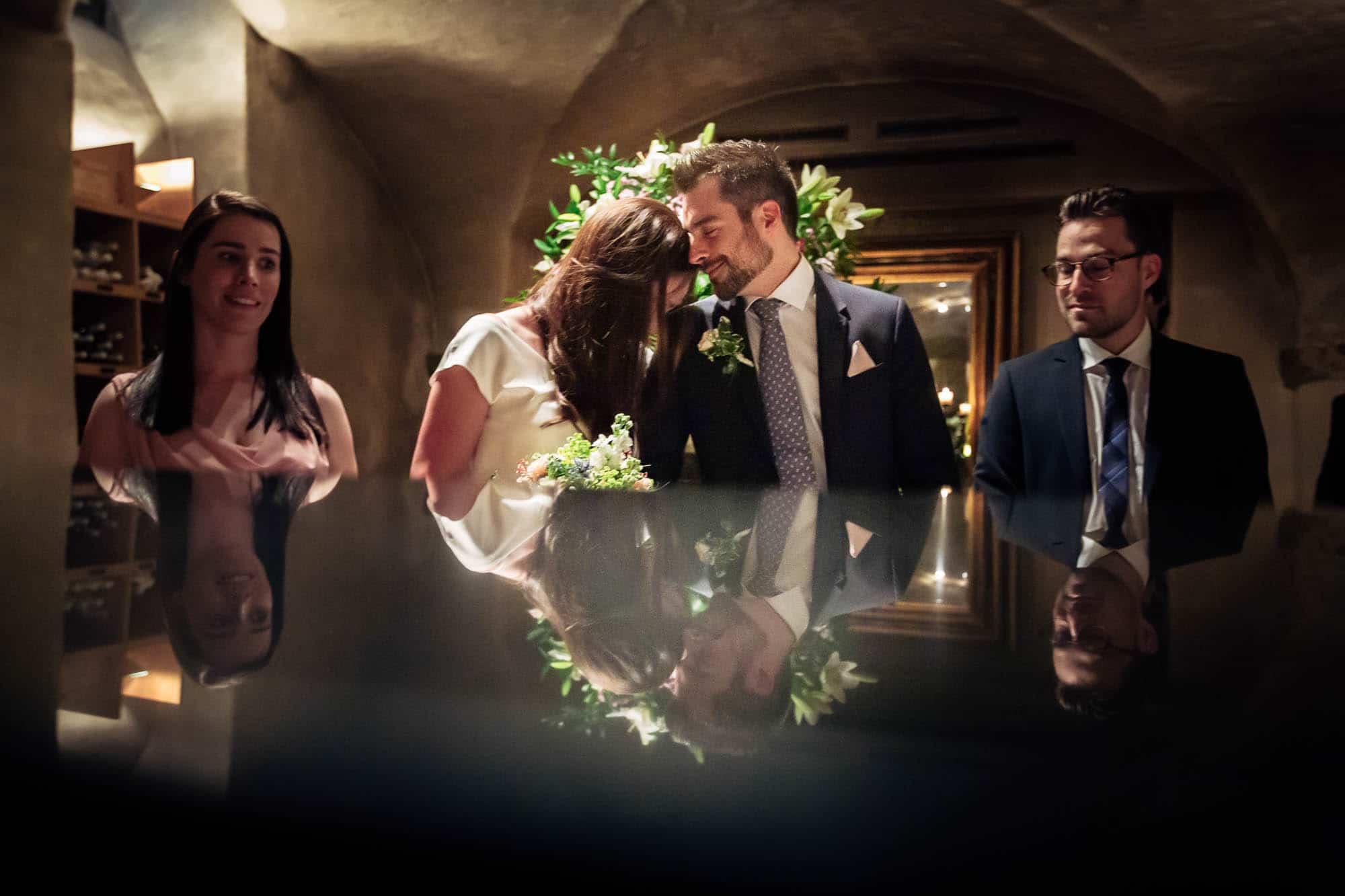 Brautpaar spiegelt sich während Trauung auf Tresen