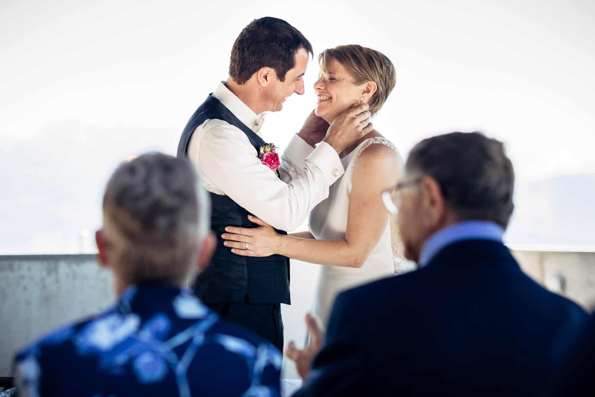 Bräutigam hält Braut um den Hals fest für den Kuss