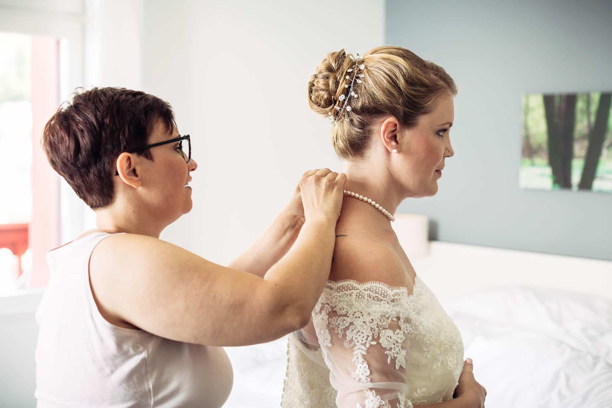 Trauzeugin legt der Braut Schmuck an