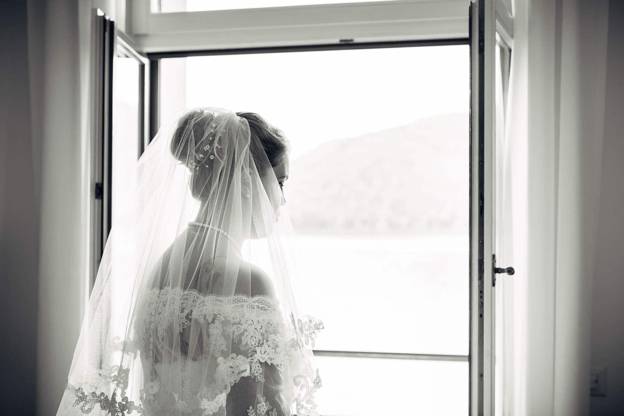 Braut schaut aus dem Fenster vom Vitznauerhof auf den Vierwaldstättersee