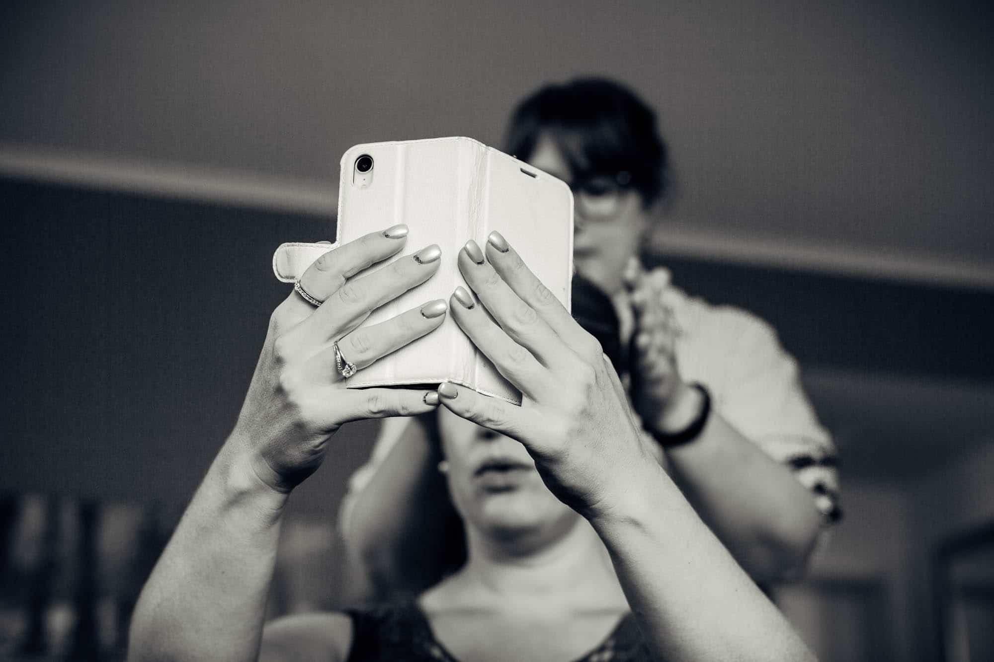 Braut kontrolliert die Frisur mit Selfie Cam