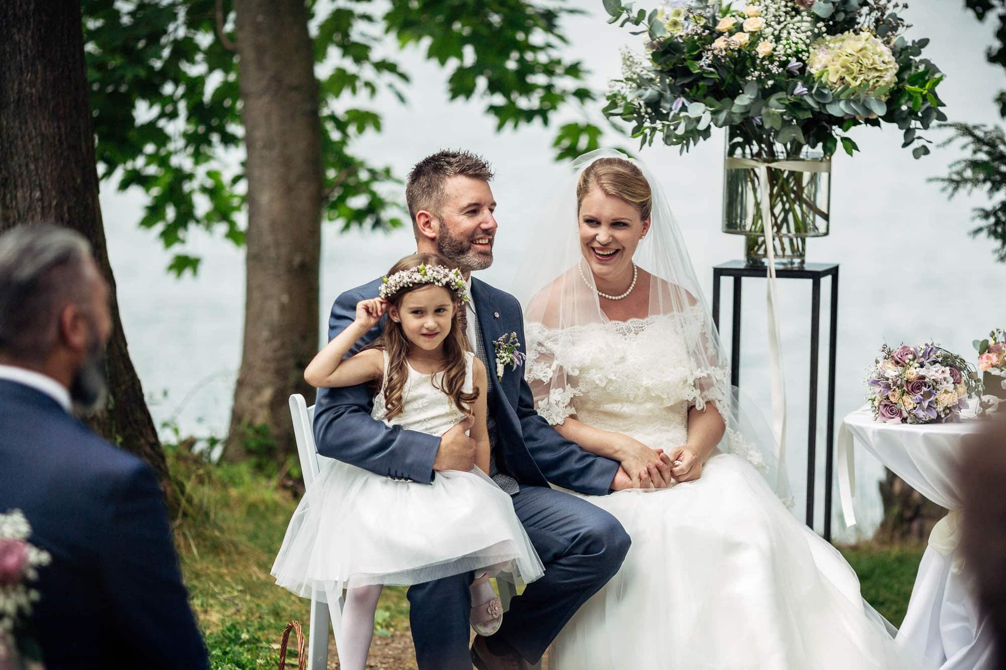 Hochzeitszeremonie am See. Brautpaar lacht.