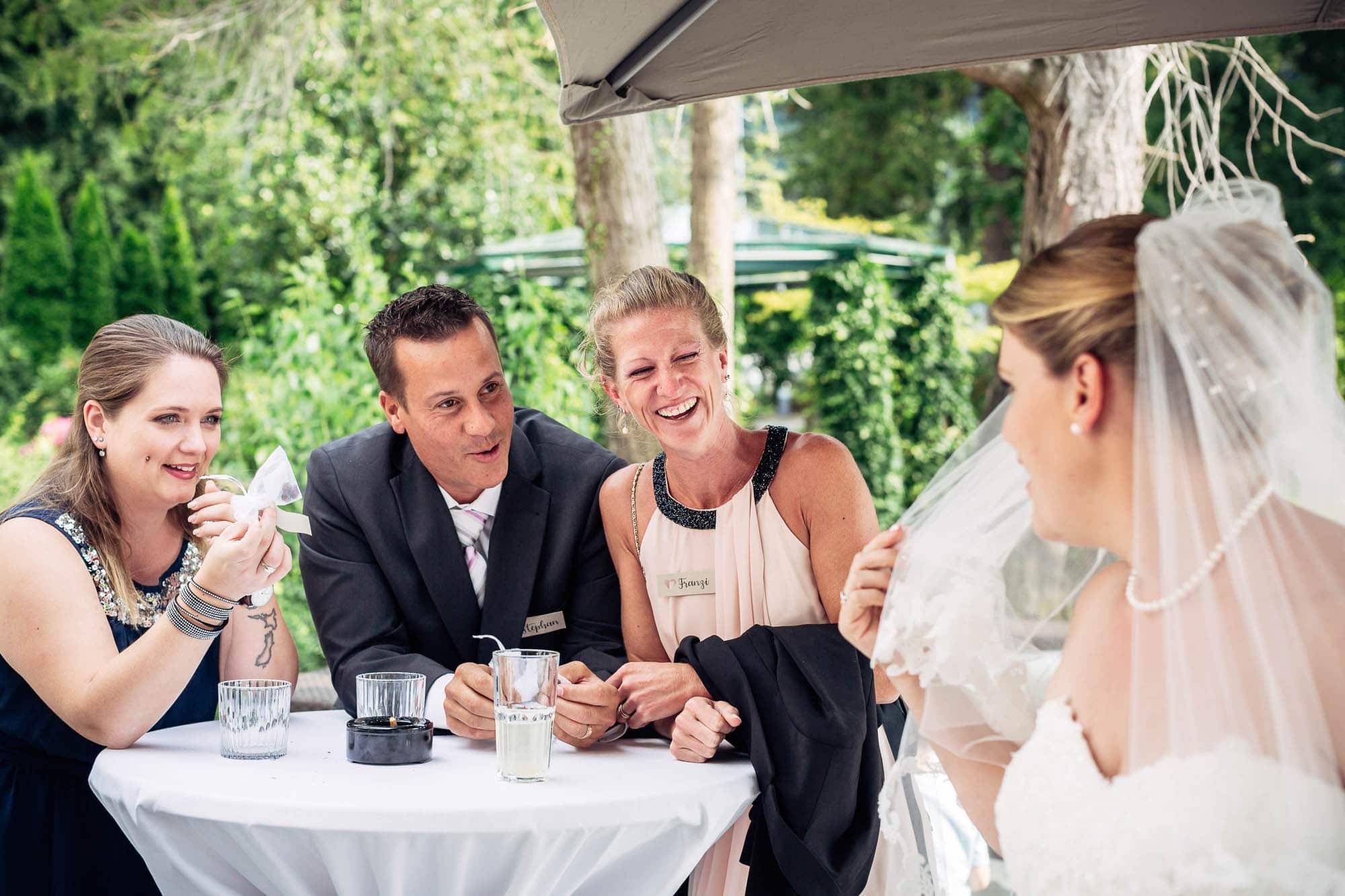 Gäste erzählen ein Wortspiel und lachen über einen Witz