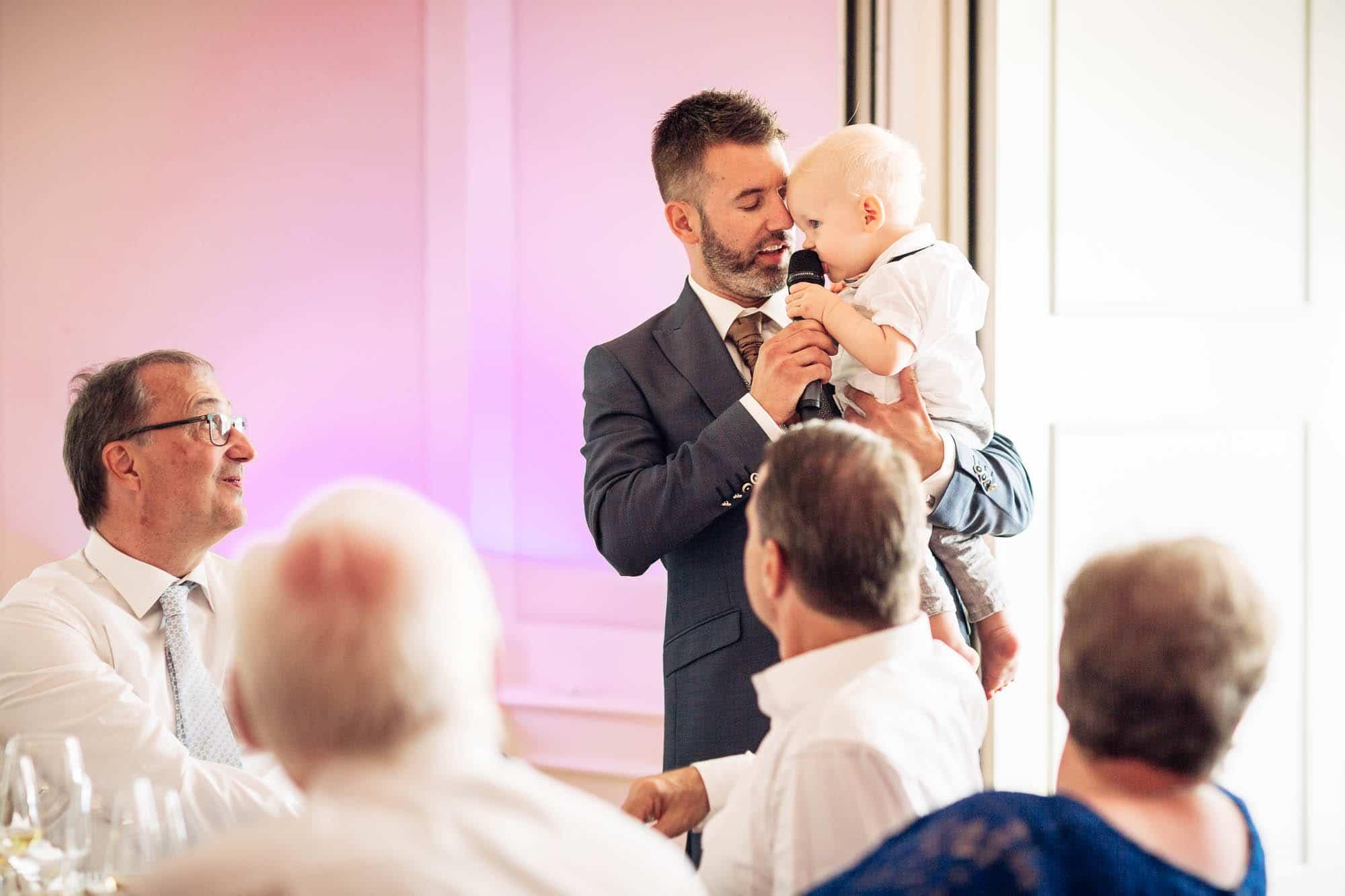 Bräutigam hält Ansprache mit Baby am Mikrofon