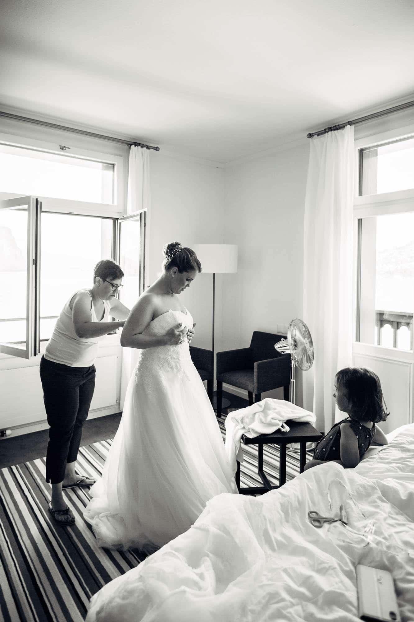 Braut wird angezogen mit Brautkleid