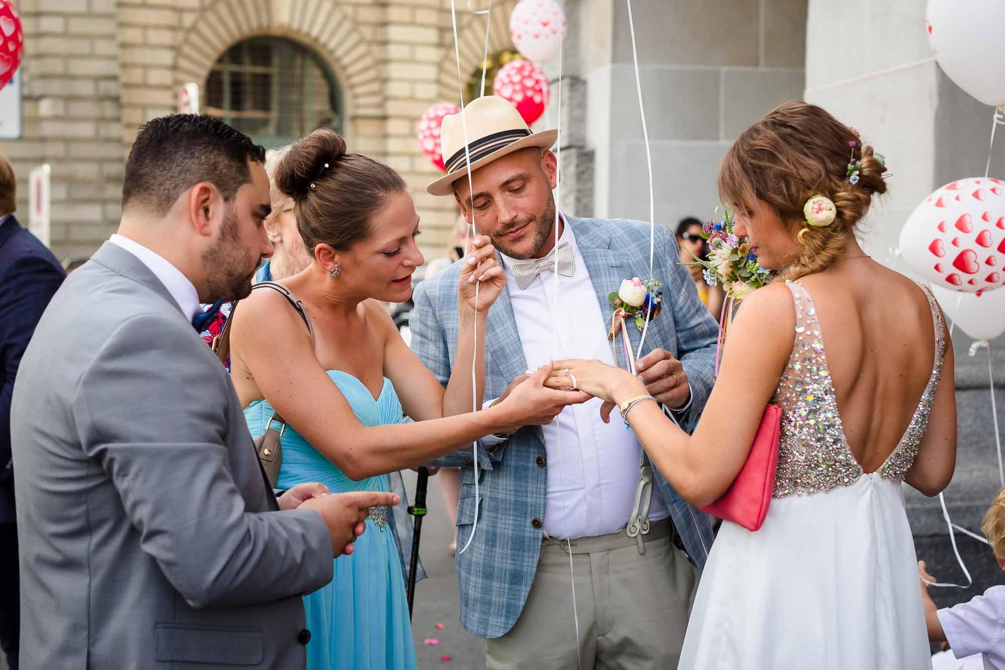 Gäste schauen Ehering der Braut an