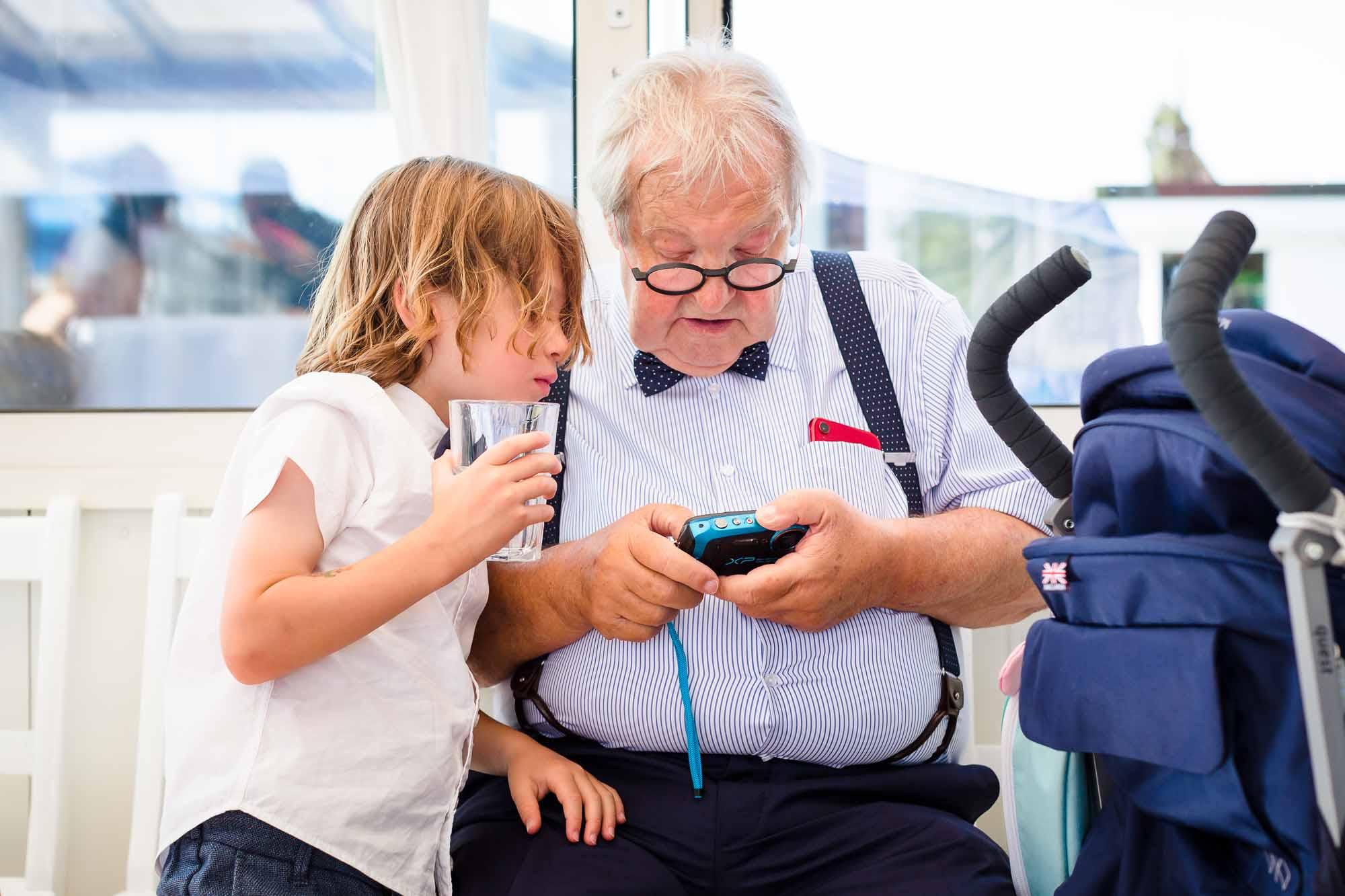 Mann und Kind schauen ins Handy