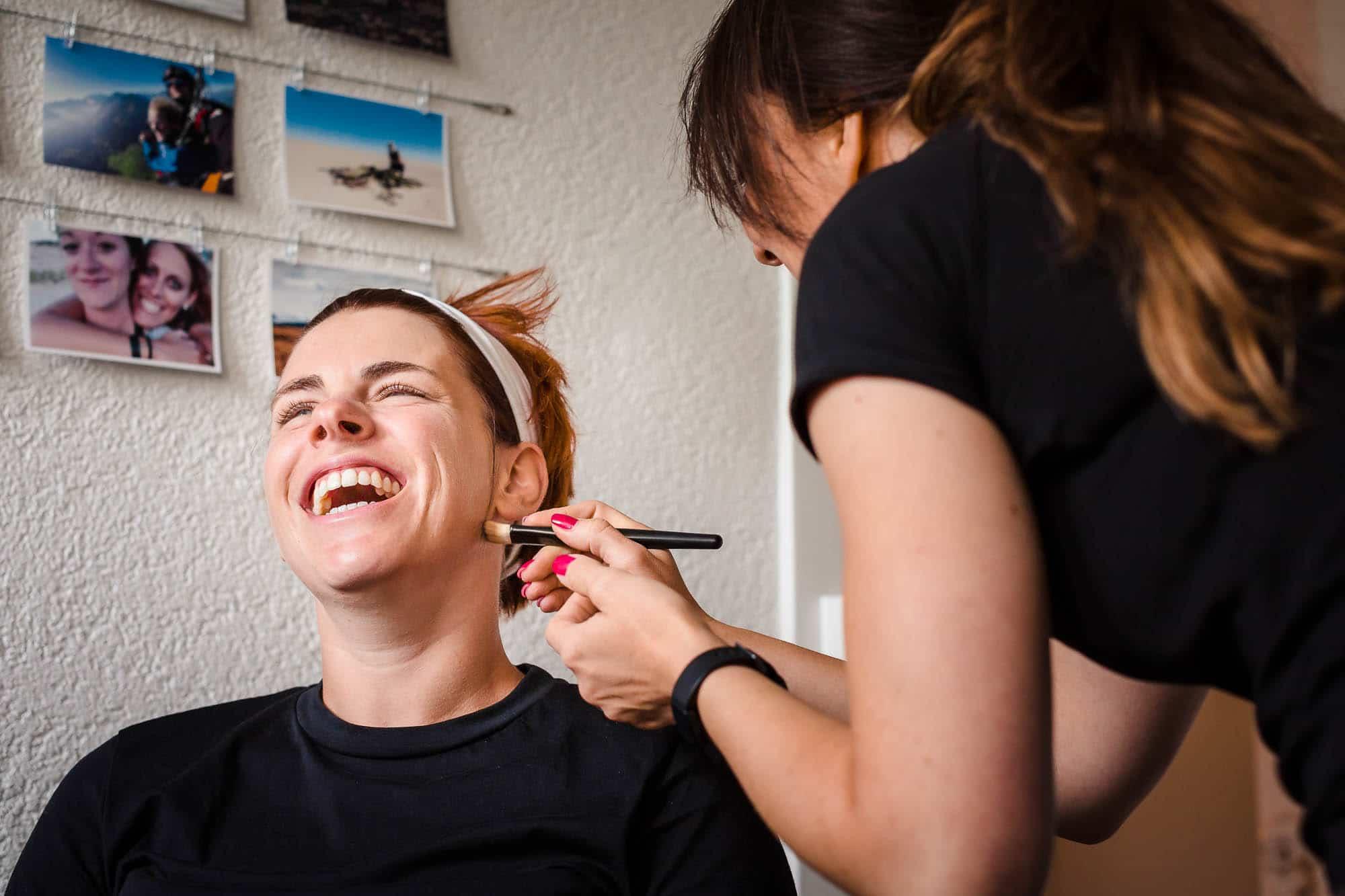 Braut lacht während sie geschminkt wird