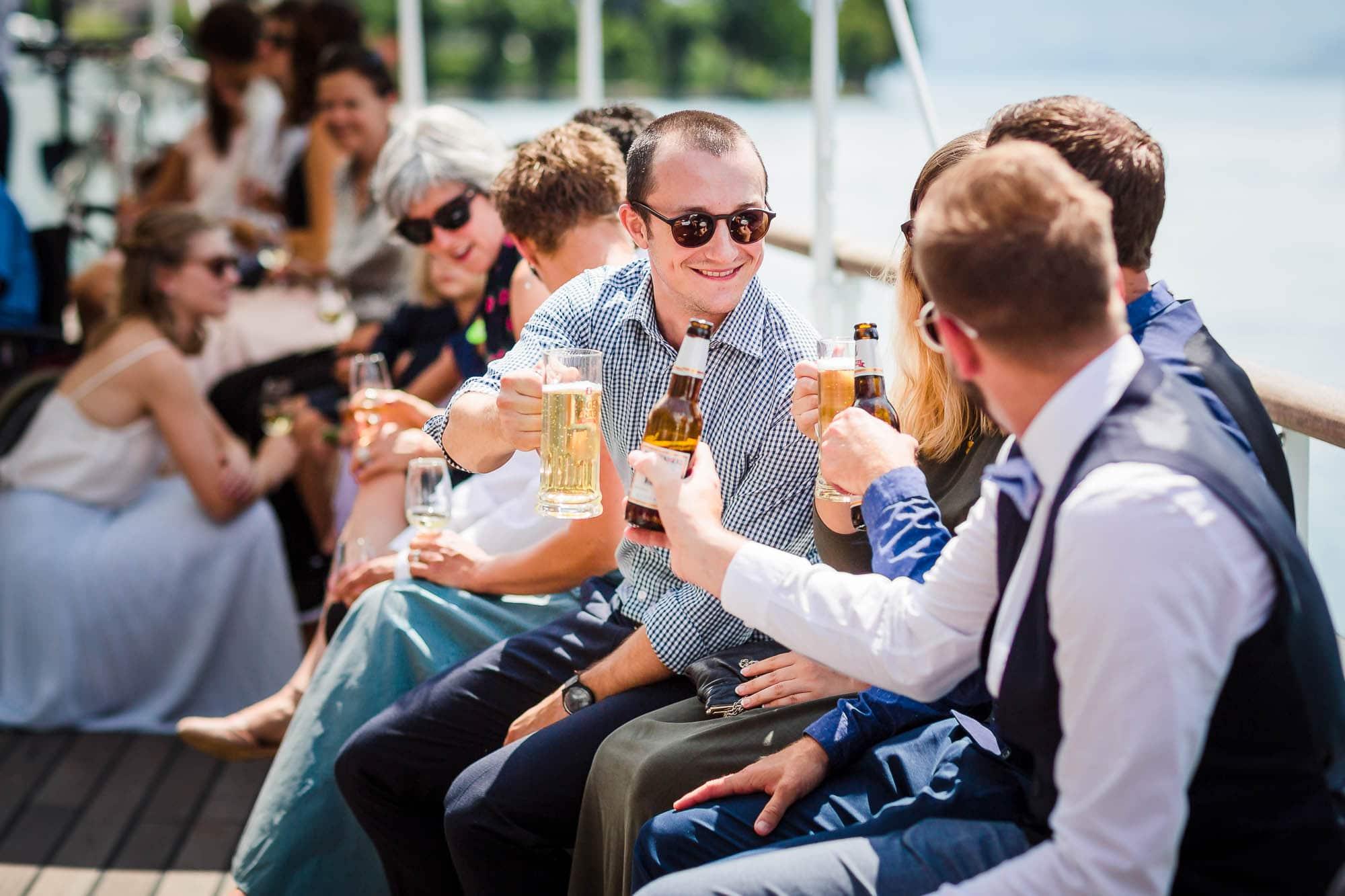 Gäste stossen mit einem Bier an auf Schiff