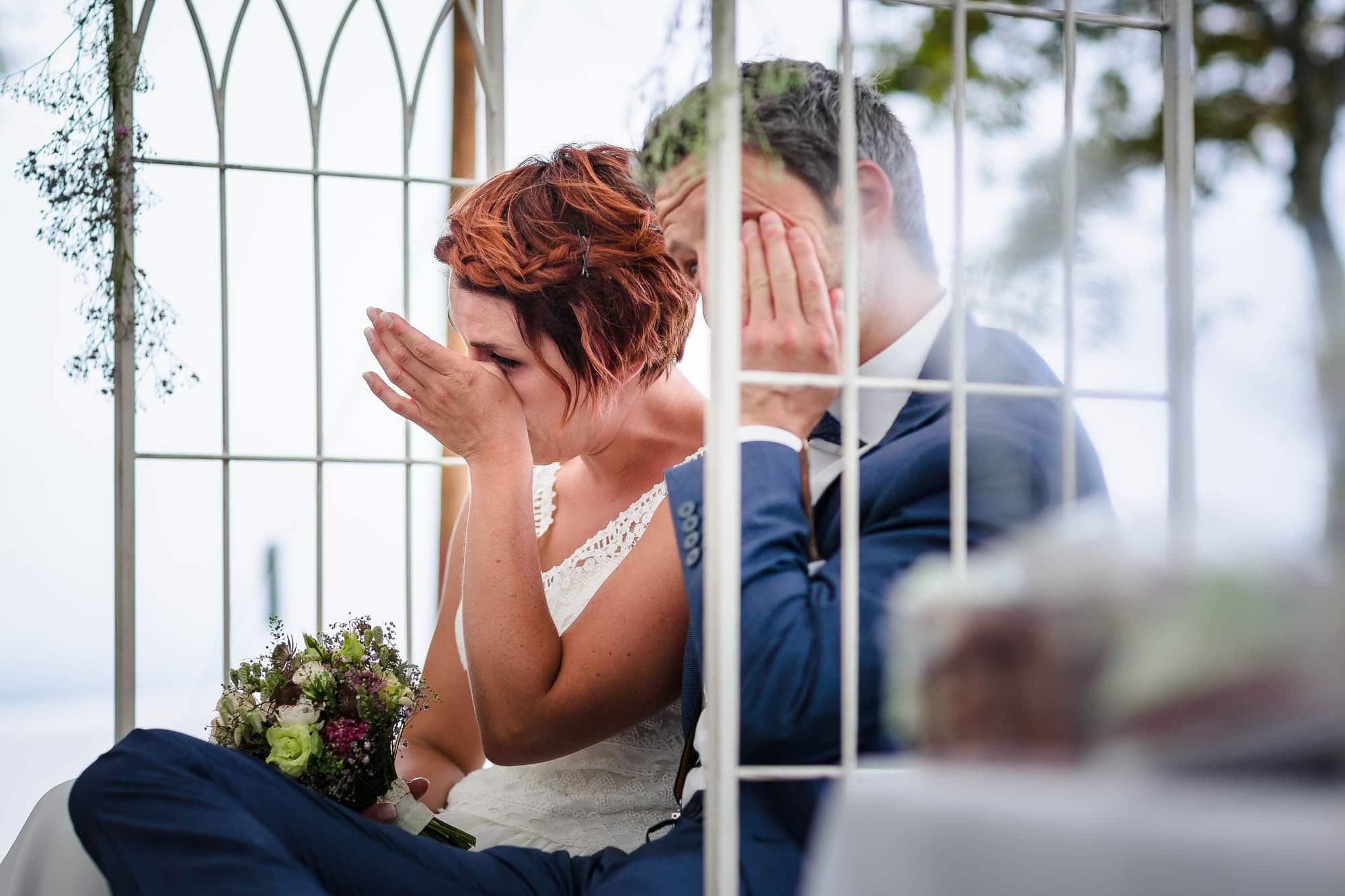 Braut und Bräutigam reiben sich Freudetränen von den Augen