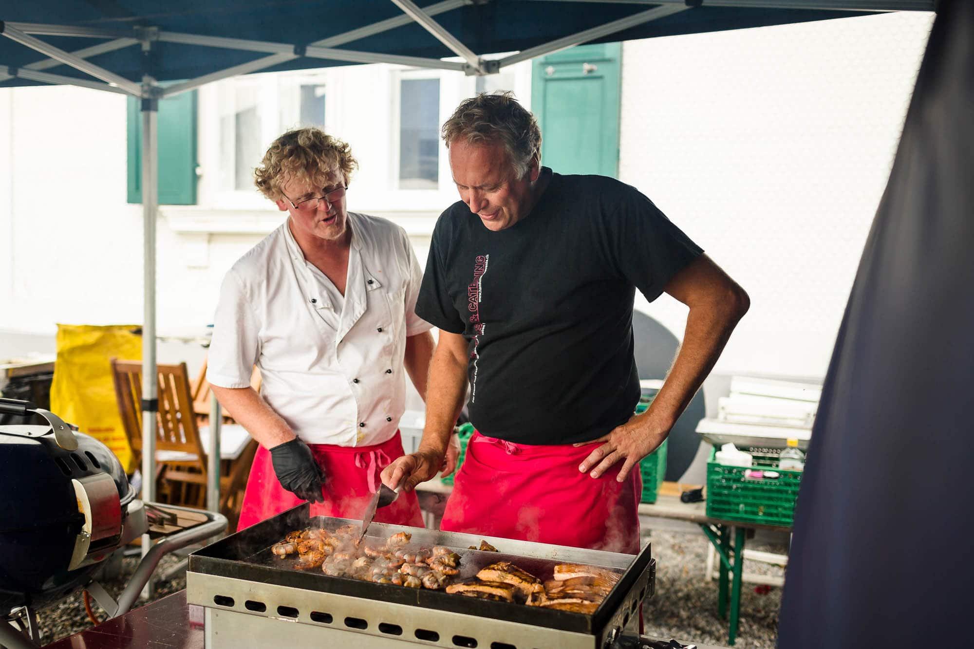 Das Grillbuffet wird vorbereitet und Fleisch grilliert