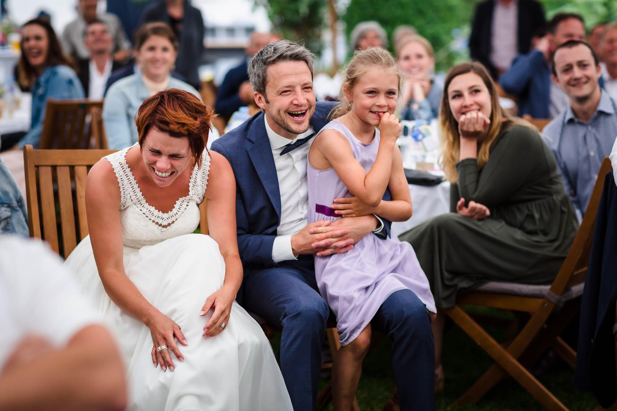 Hochzeitspaar und Gaste lachen herzhaft