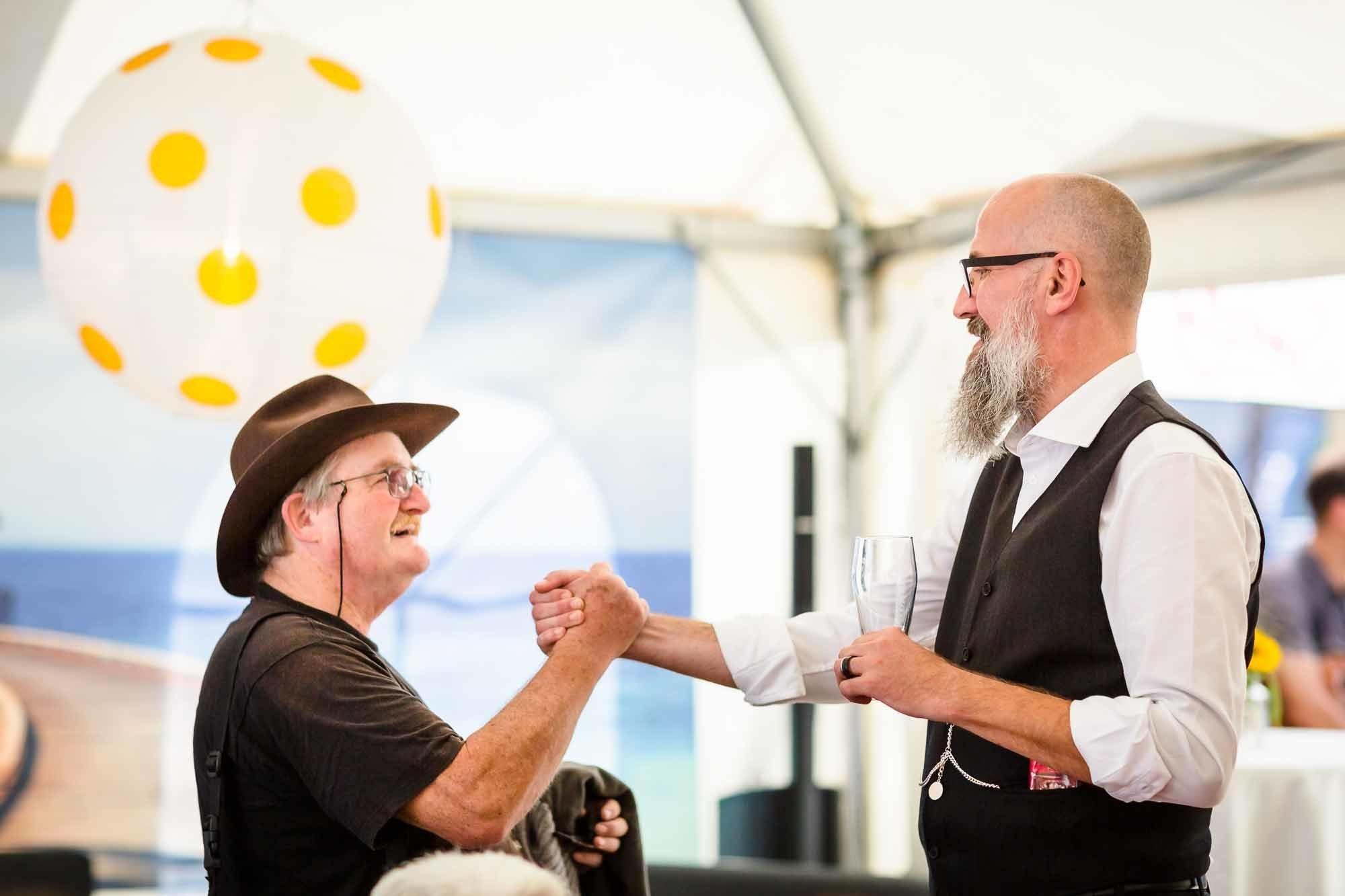 Bräutigam und Gast geben sich Handschlag