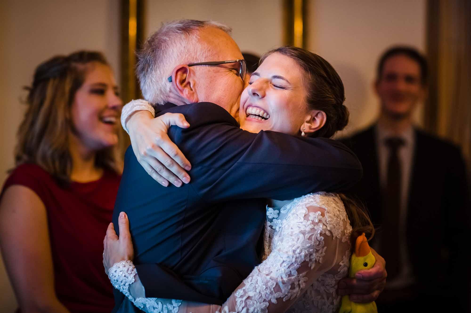 Braut umarmt Gast und lacht dabei