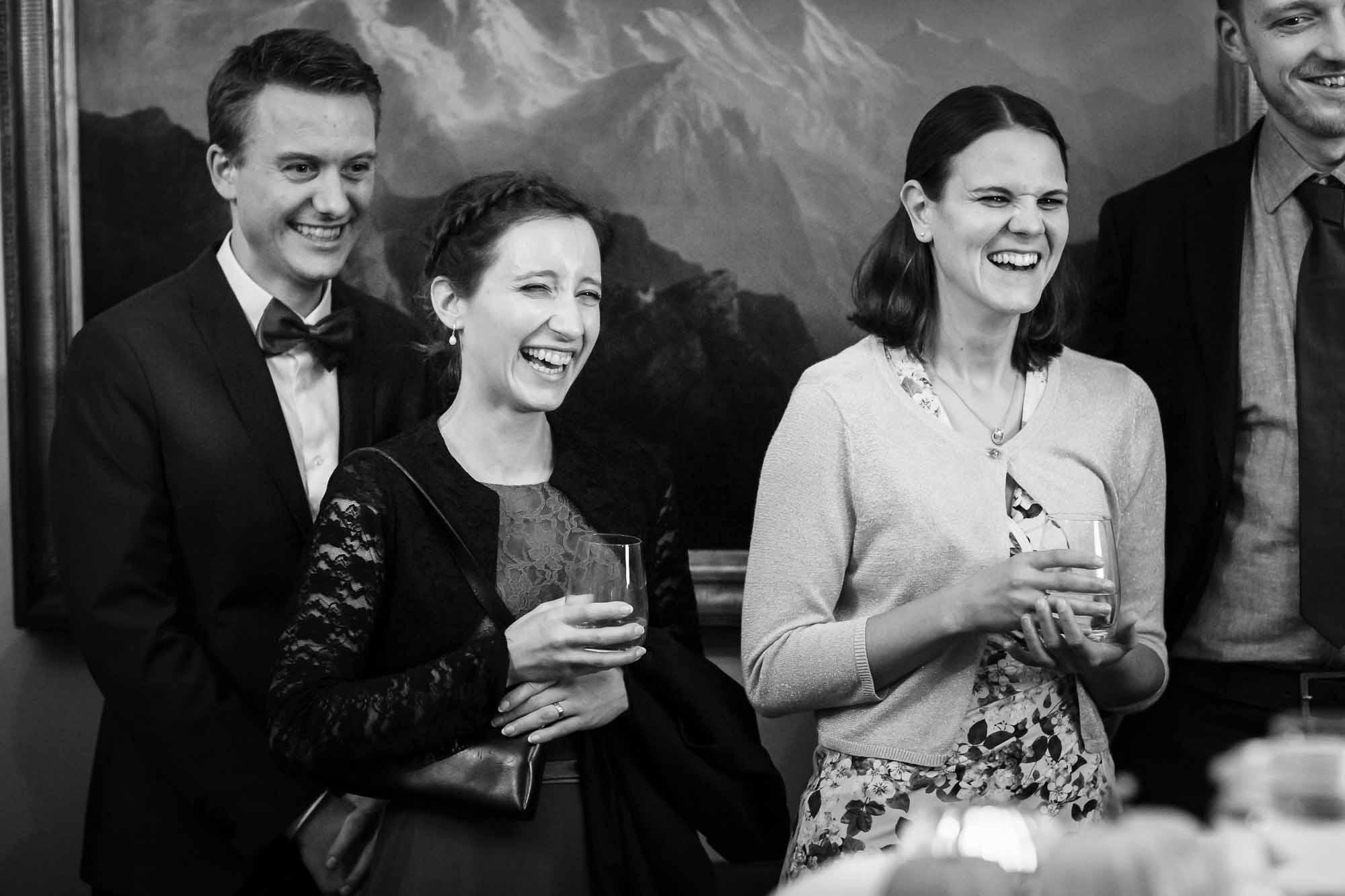 Hochzeitsgäste lachen während Präsentation