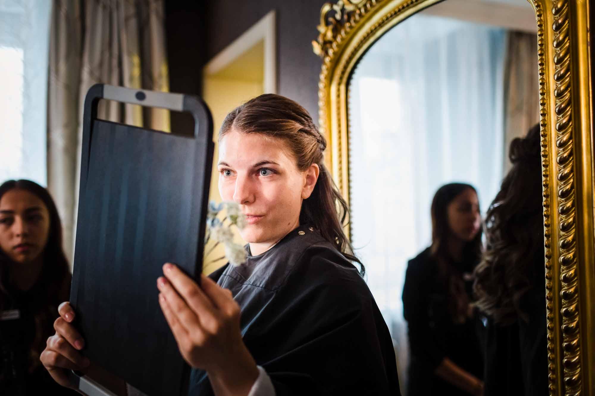 Braut kontrolliert Frisur im Spiegel