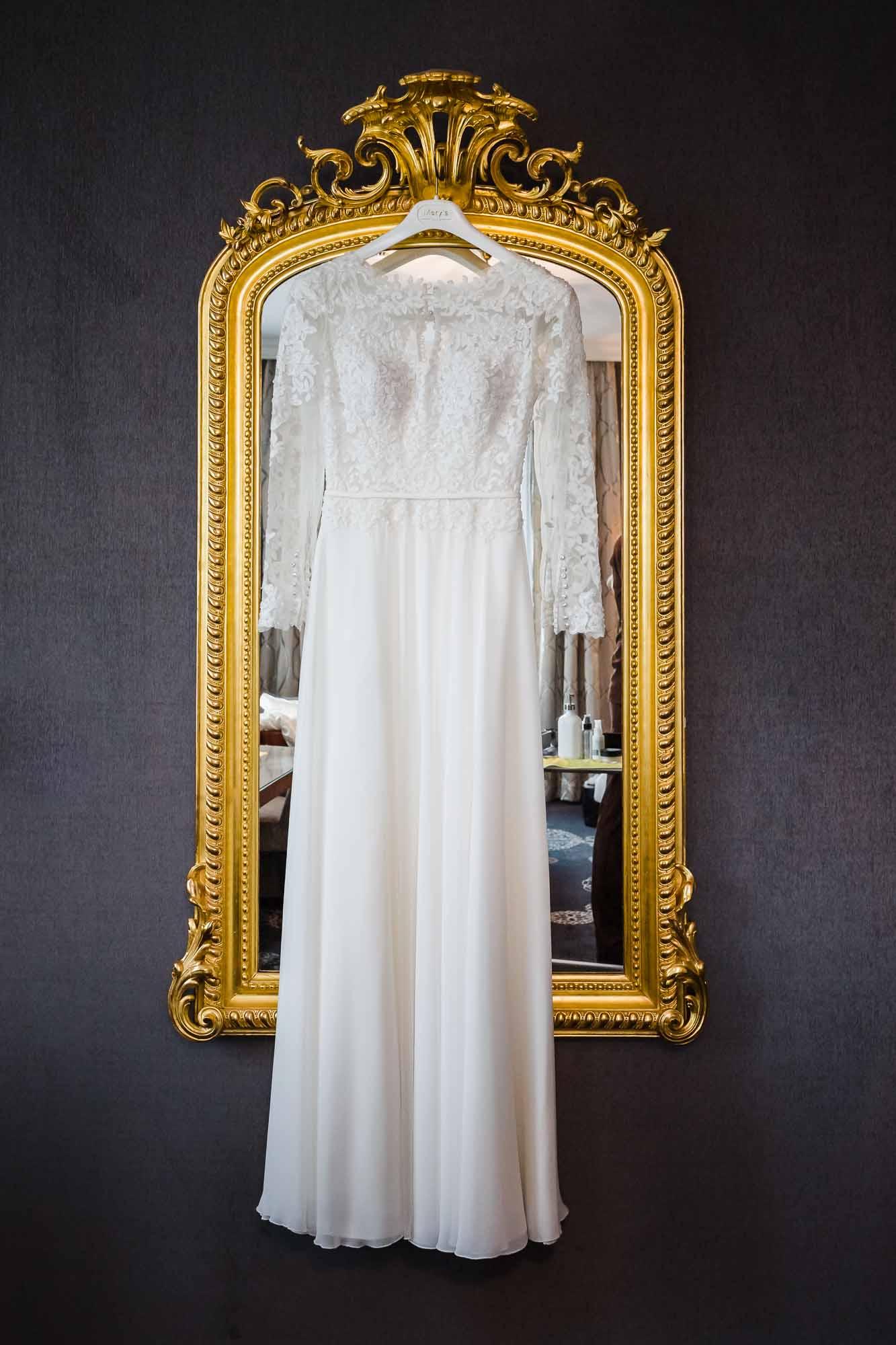 Hochzeitsbilder Luzern. Brautkleid hängt vor goldenem Spiegel im Schweizerhof