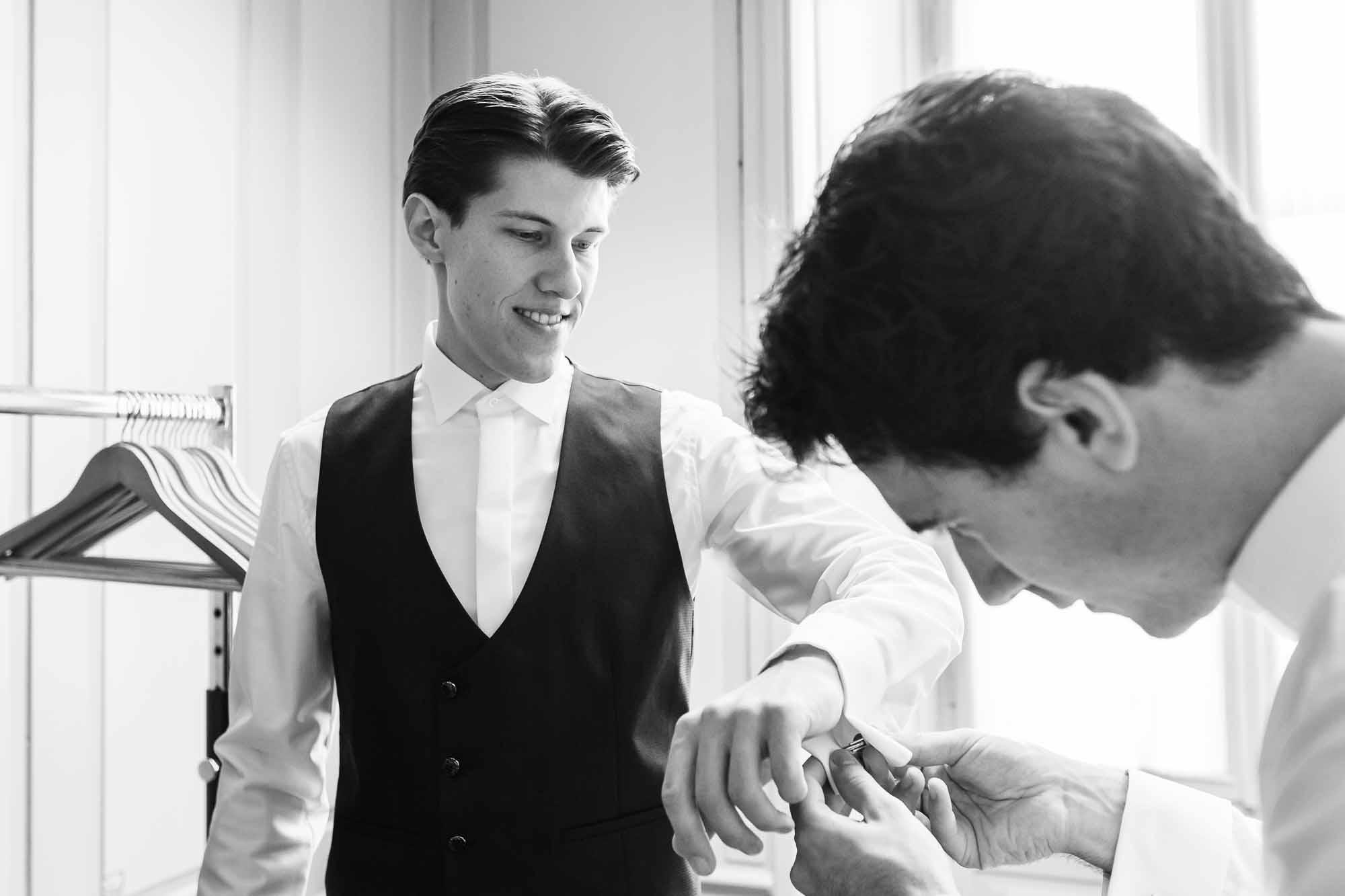 Trauzeuge steckt dem Bräutigam die Manschettenknöpfe an