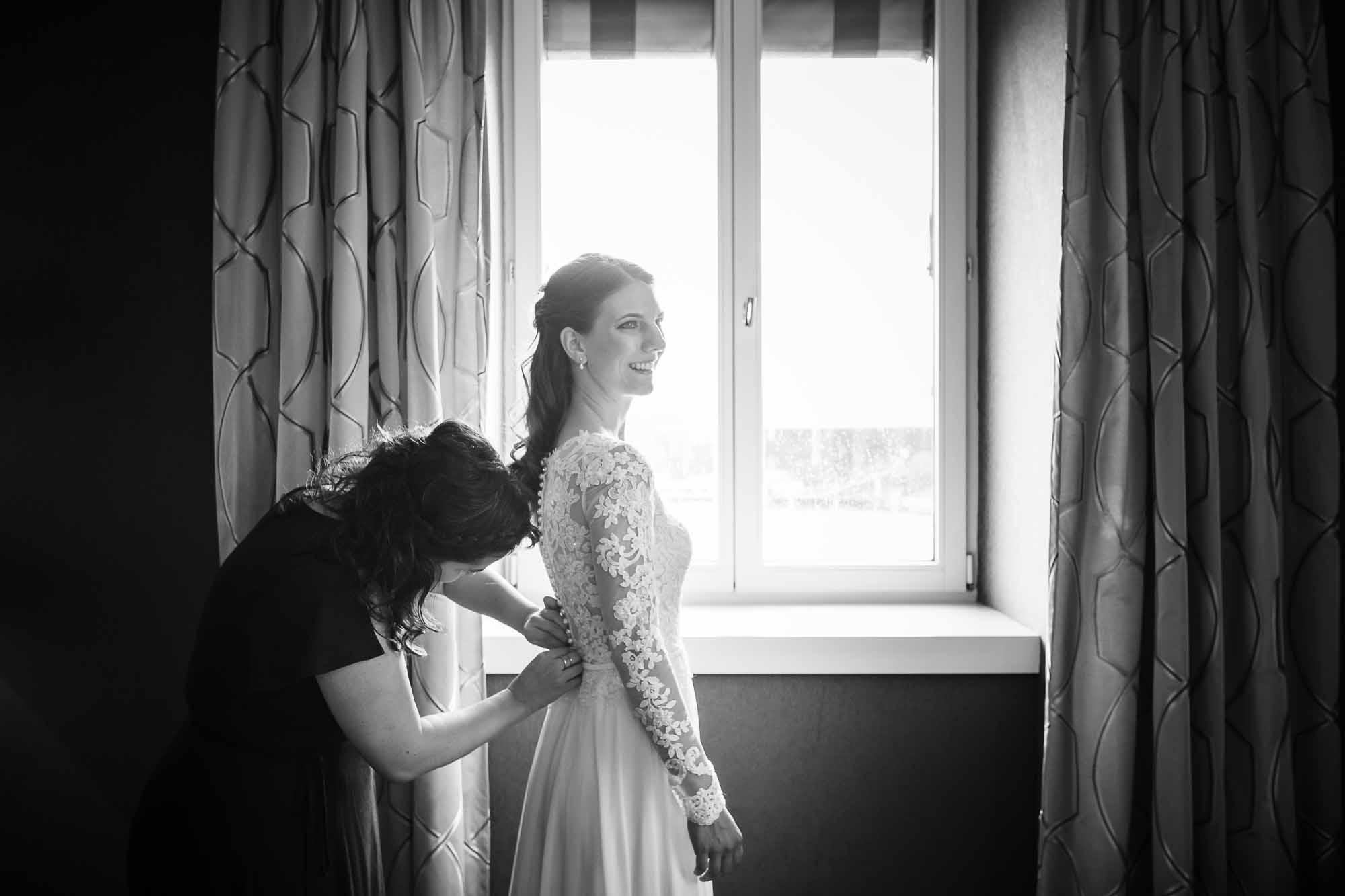 Braut wird angezogen vor Fenster Hochzeitsbilder Luzern