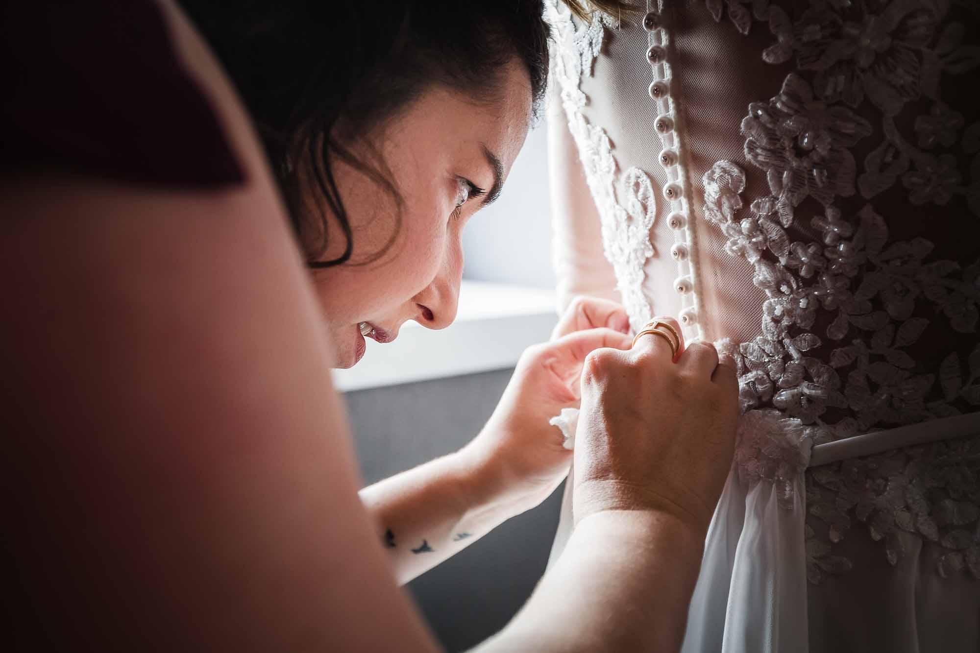 Hochzeitskleid wird zugeknöpft