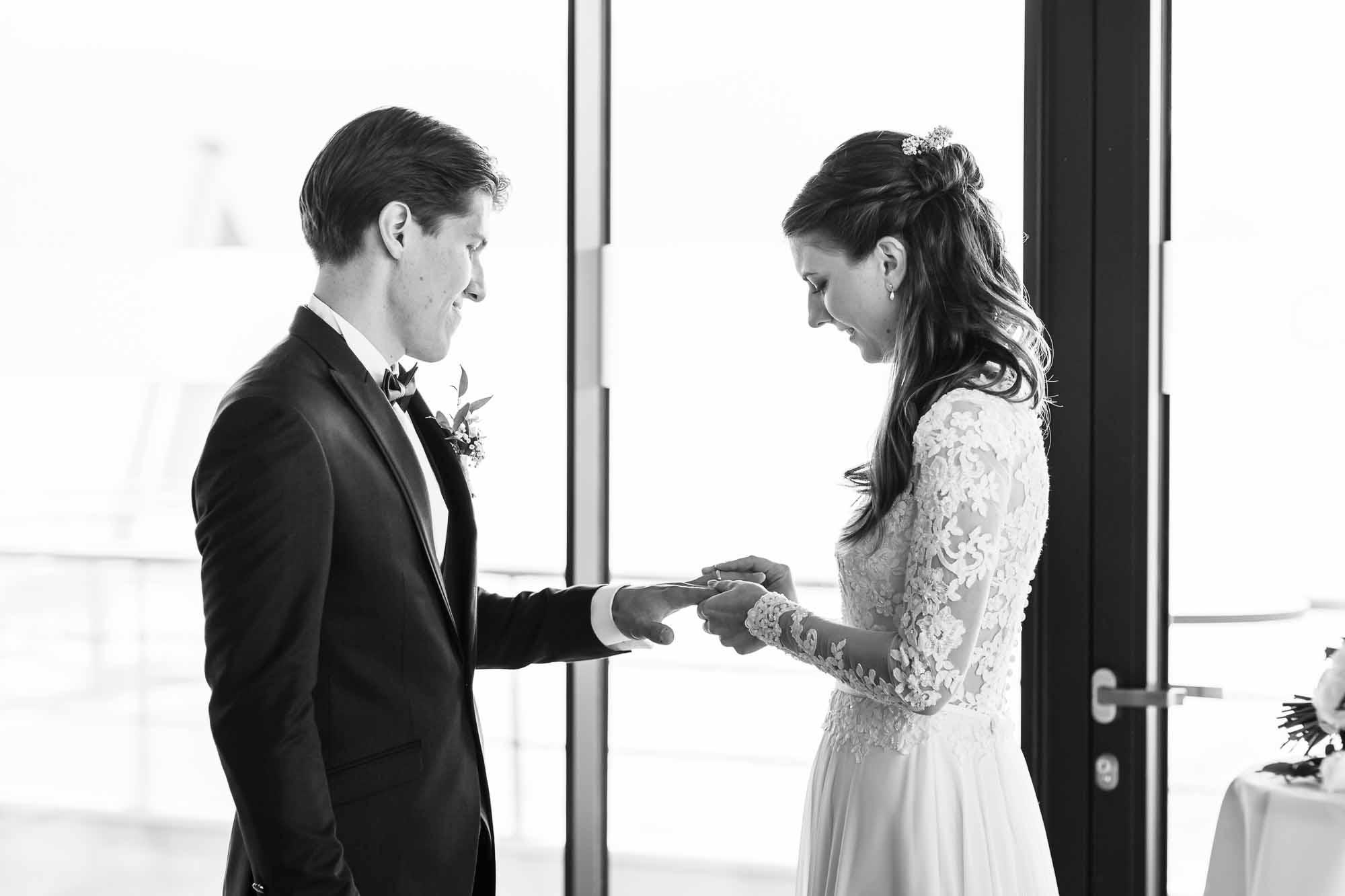 Braut steckt dem Bräutigam den Ring an