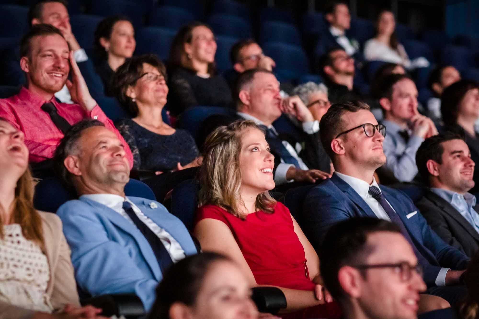 Hochzeitsgäste lachen während IMAX Film