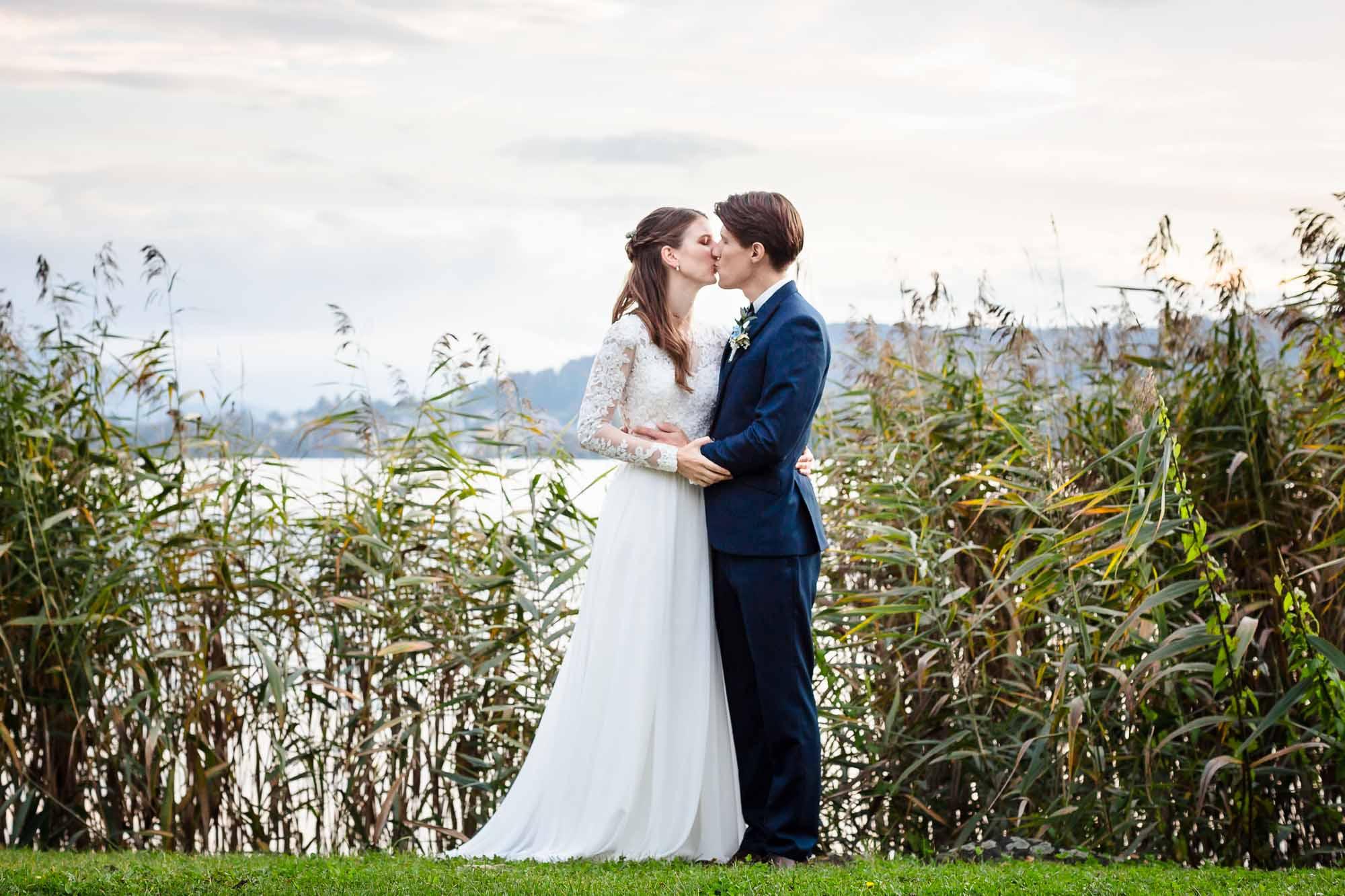 Hochzeitsfotos Luzern Brautpaar küsst sich vor Schilf
