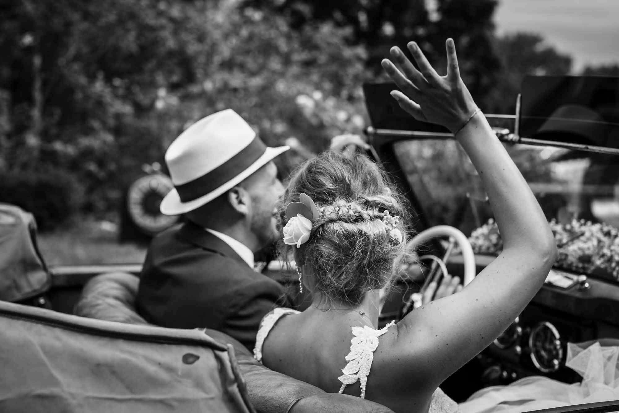 Brautpaar fährt mit Oldtimer davon und winken