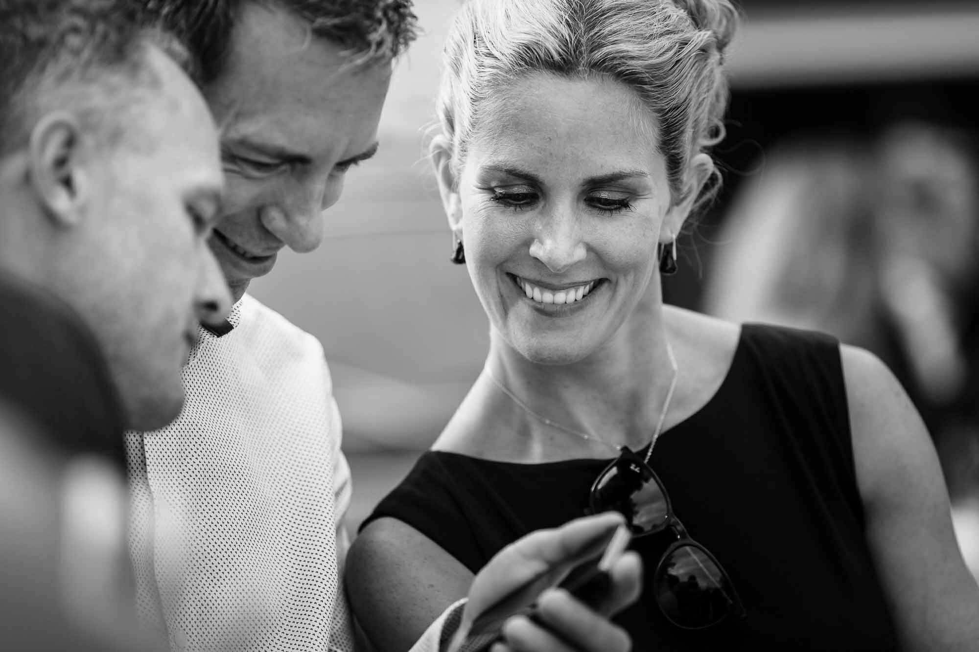 Gäste lachen über Bild auf Handy