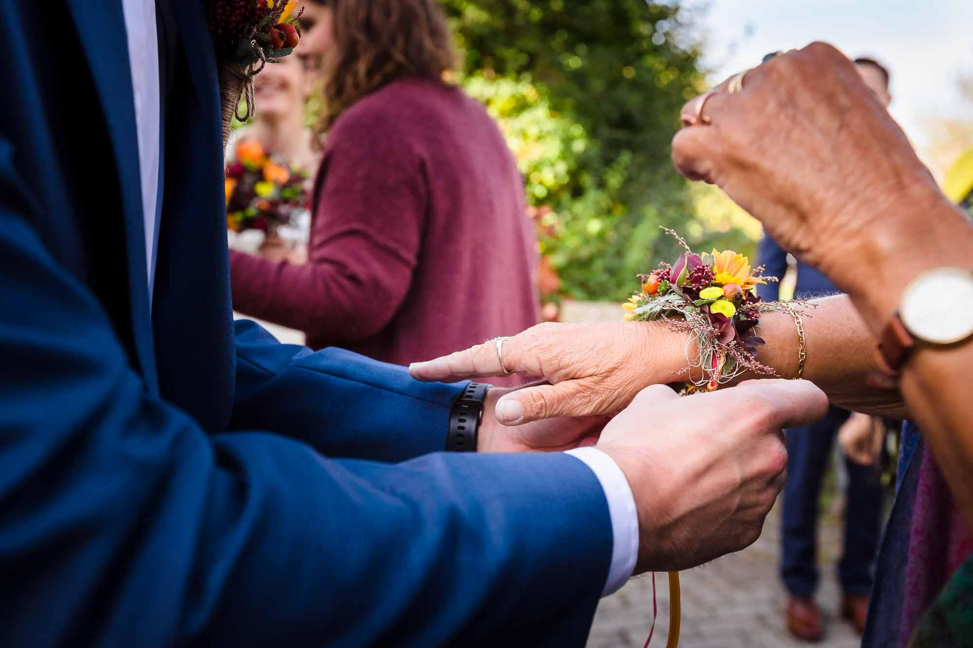 Blumenschmuck wird ums Handgelenk gebunden